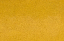 Hardboard. Bumpty Surface, Texture Of Construction Material Close-up. Flip Side Of Hardboard. Yellow Background.