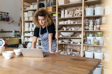 Ženska umjetnica keramike koja koristi laptop u umjetničkom studiju