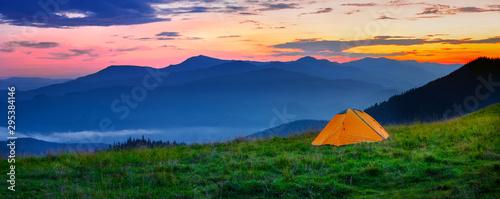 Obraz na plátně Orange tent in the mountains at sunset