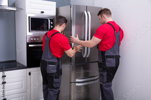 Two Young Male Movers Placing Steel Refrigerator In Kitchen Canvas Print