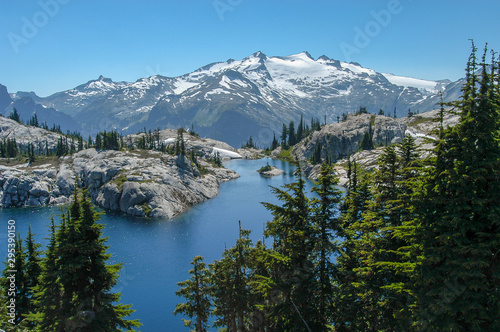 Robin Lake surrounded by granite and trees with snow-capped Mt Canvas Print