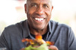 African American man eating a burger without a bun.