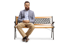 Bearded Man Sitting On A Bench...