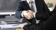Businessman shaking hands with his colleague or partner above the glass desk in modern office, close-up. Unknown business people at meeting. Teamwork, partnership and handshake concept