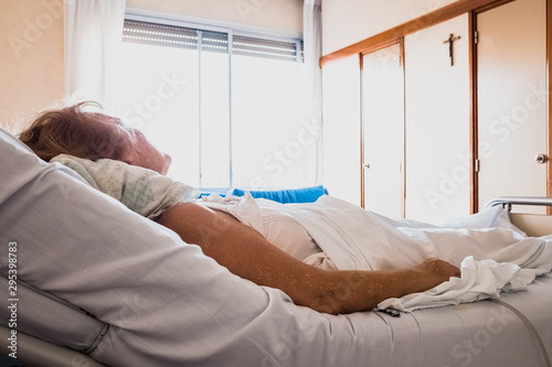 Older woman lying in hospital bed alone looking at the Christian crucifix asking for her healing Wallpaper Mural