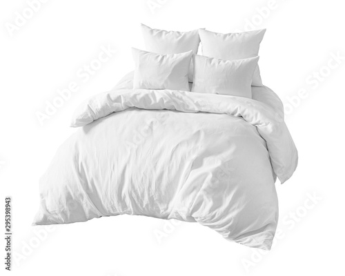 Photo White bedding items on the bed isolated.