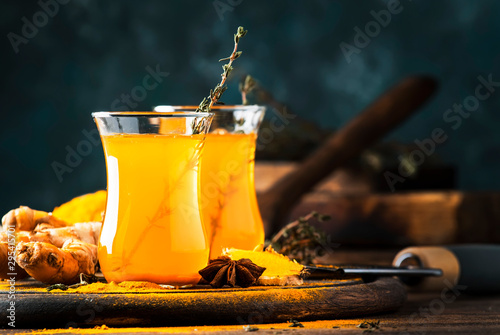 Healthy vegan turmeric golden tea with honey in glass cup on wooden tray. Herbal healing spicy tea