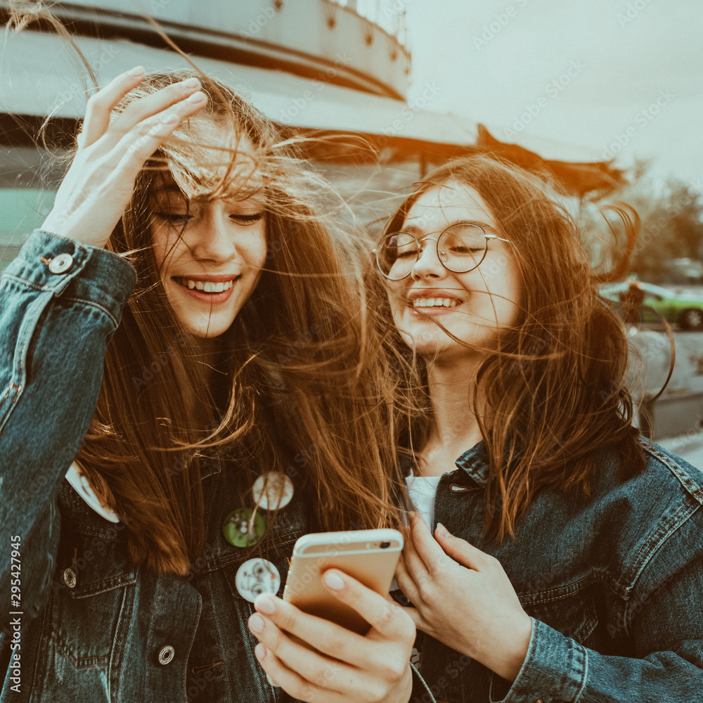 Fototapety, obrazy: Happy young best friends using social media on their smartphon