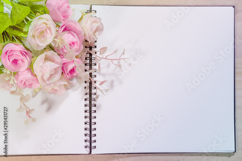Fotografía  open note book with pink rose flowers on wooden background
