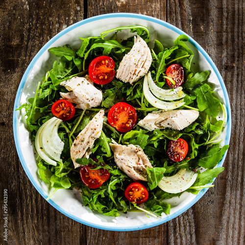Salad with chicken meat and arugula on wooden table