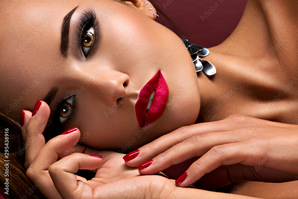 Fototapeta Beautiful  woman with bright eye makeup and  red lips lying on the sofa