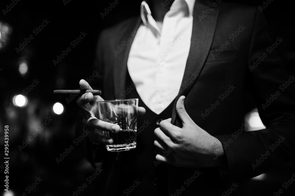 Fototapeta Close up hand of handsome well-dressed arabian man with glass of whiskey and cigar posed at pub.