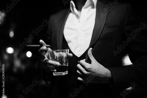Tablou Canvas Close up hand of handsome well-dressed arabian man with glass of whiskey and cigar posed at pub