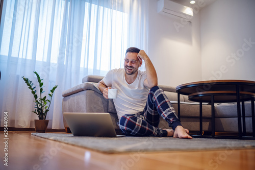 Charismatic smiling caucasian man in pajamas sitting on the floor in living room, leaning on sofa, holding mug with coffee and looking at laptop. Weekend activities concept. - 295440964
