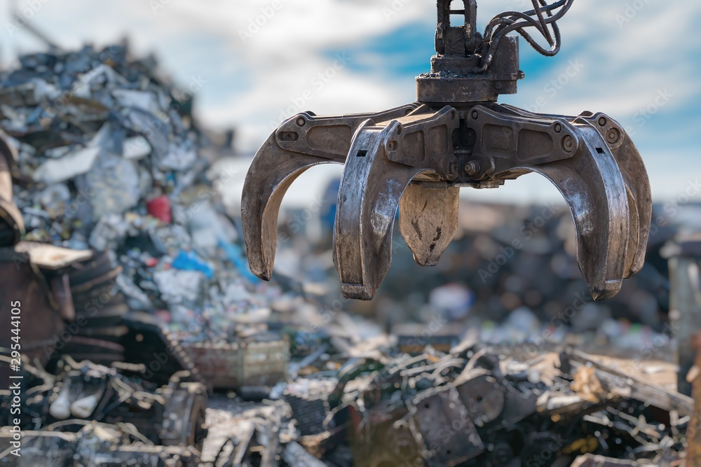 Fototapeta Close-up view on mechanical arm claw of crane at landfill.