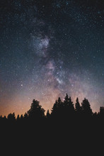 Silhouette Of Pine Trees In The Mountains And Night Sky View With Stars And Milky Way Galaxy View At A Midnight Hiking Nature Trip. Wurmberg, Braunlage Harz National Park, German Mountain