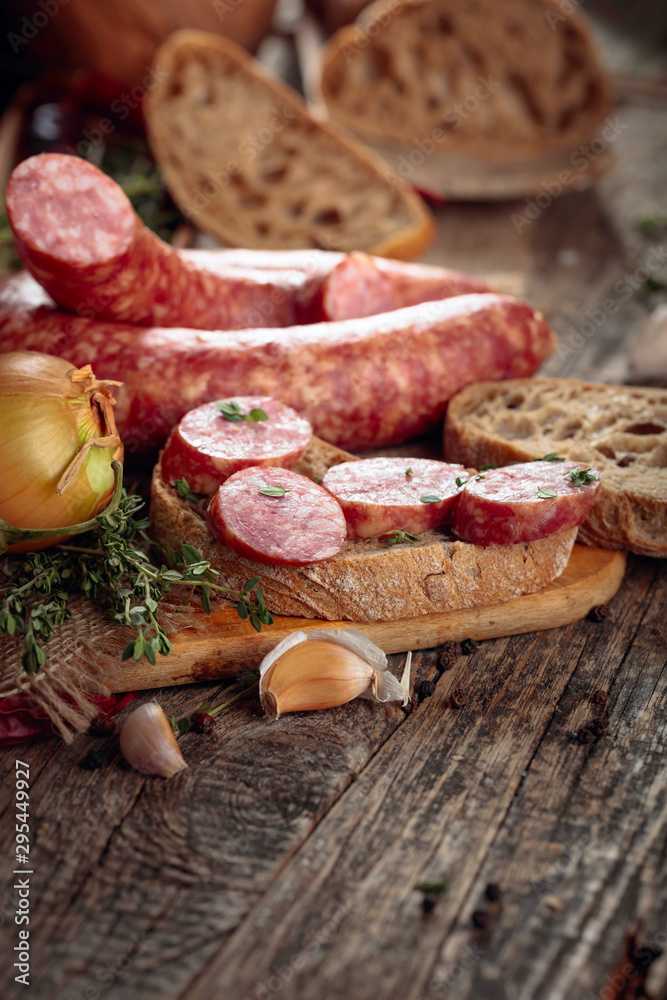 Fototapety, obrazy: Dry-cured sausage with bread and spices on a old wooden table.