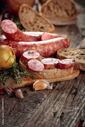 Dry-cured sausage with bread and spices on a old wooden table. Canvas Print
