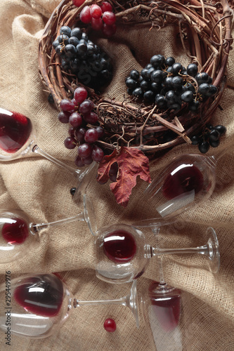Fotografie, Obraz  Red wine and grapes on a table covered with burlap.
