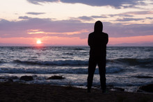 Solitude, Loneliness, Mindfulness Concept. Silhouette Of Young Man Standing On Edge Of Beach And Looking To Horizon Of Sea Waves. Dreaming And Thinking Alone Person At Sunset Seashore.