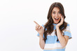Enthusiastic joyful surprised woman introduce incredible offer, pointing finger left copy space, smiling joyfully and impressed look camera, touch cheek astonished, white background