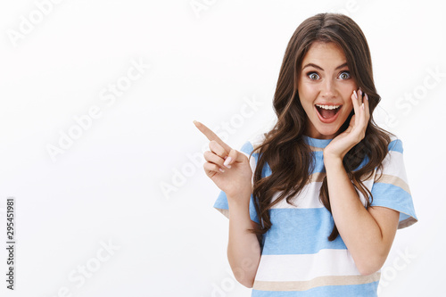 Enthusiastic joyful surprised woman introduce incredible offer, pointing finger Slika na platnu