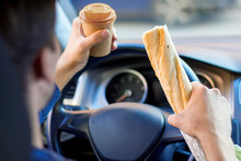 Driver Is Eating Baguette And Drinking Coffee Behind Steering Wheel Of Car. Young Man Is Not Attentively Driving Automobile. Guy Is Breaking Rules Of Road. Concept Of Fast Rhythm In Modern City.