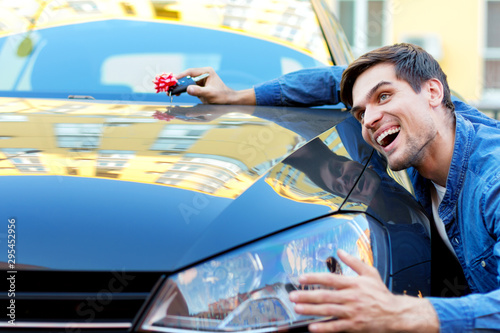 Fotomural  Happy cheerful owner of new black car is holding gift, surprise, keys with red bow
