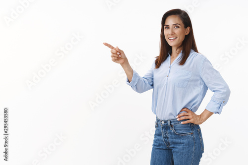 Fotomural  Confident good-looking motivated businesswoman stand half-turned office, pointin
