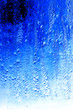 Leinwandbild Motiv Drops on glass on a blue background
