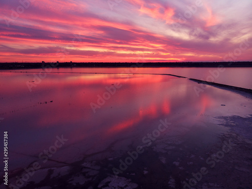 Foto auf Gartenposter Hochrote Aerial view of drone shot over water surface in twilight, golden hour sunset. Amazing view, firth surface reflecting majestic red and pink clouds