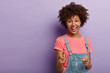 canvas print picture - Positive young curly woman selects you, points with both index fingers at camera, smiles happily, wears casual clothes, being glad and satisfied, stands against purple background. You are my type