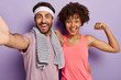 canvas print picture - Indoor shot of joyful diverse couple keep muscle flexible, live healthy life, have daily workout, wear sports clothing stand closely look at camera with happy expression show biceps motivated to sport