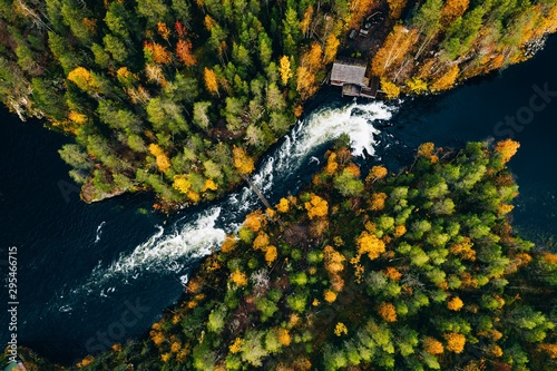 Fototapeta Aerial view of fast river flow through the rocks and colorful forest