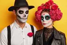 Participants Of Parade In Mexico, Prepare To Most Popular Holiday, Wears Skull Makeup, Black And White Clothes, Isolated Over Yellow Background. Serious Vampires Celebrate Halloween Together