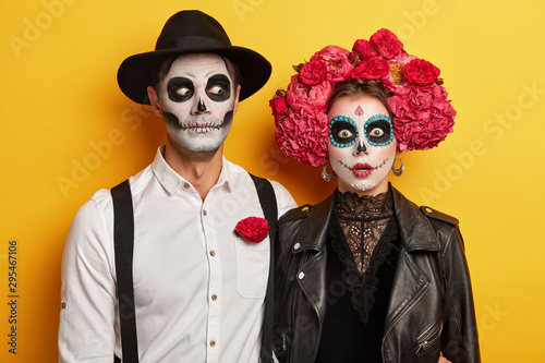 Scarying undead couple celebrate mexican holiday to remember dead relatives, dressed in carnival costume, wears skull makeup, red flowers as symbol of this event Wallpaper Mural