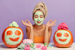 Leinwanddruck Bild - Relaxed woman gets beauty treatments, meditates indoor, poses at table with cosmetic accessories and autumn crops, applies facial masks on pumpkins, has clean healthy skin, isolated over purple wall