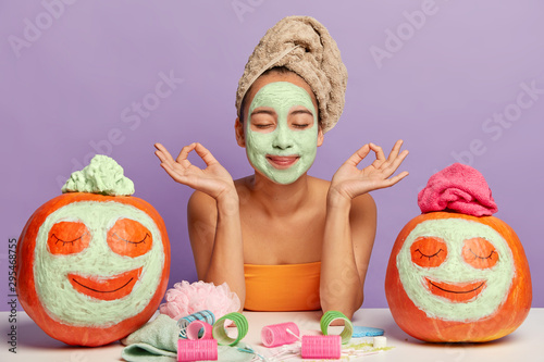 Spoed Foto op Canvas Dinosaurs Relaxed woman gets beauty treatments, meditates indoor, poses at table with cosmetic accessories and autumn crops, applies facial masks on pumpkins, has clean healthy skin, isolated over purple wall