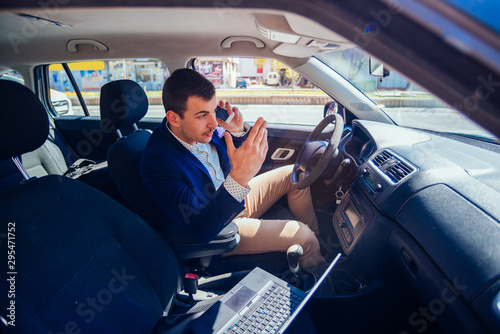 Reckless businessman driving in the city during the rush hour while typing on his laptop and acting stressed out of work Canvas-taulu
