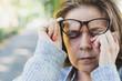 Woman rubbing her eye outdoors