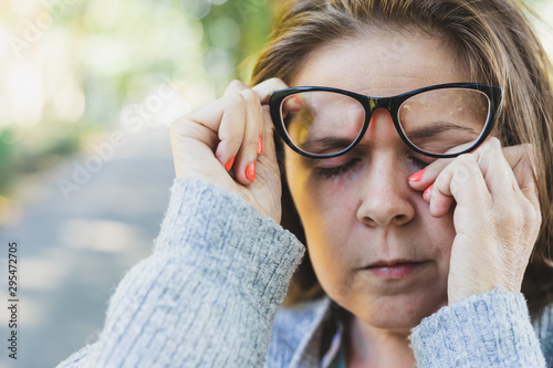 Woman rubbing her eye outdoors Canvas Print