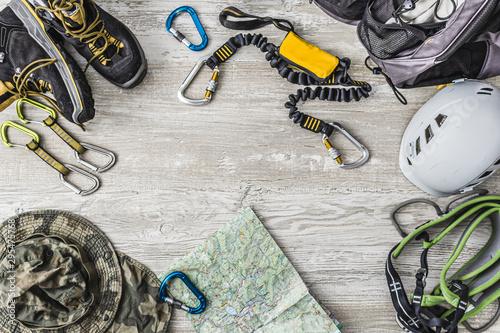 Fototapeta Pakowanie plecaka na wspinaczkę po Via Ferrata. Sprzęt wspinaczkowy ułożony na drewnianym tle. obraz