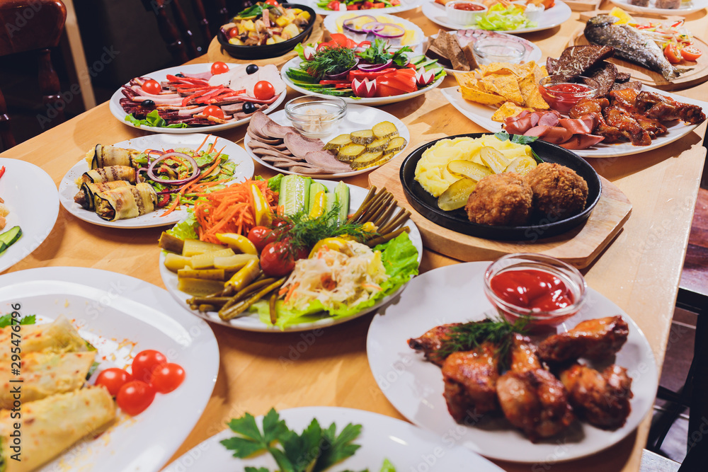 Fototapety, obrazy: Dining table with a variety of snacks and salads. Salmon, olives, wine, vegetables, grilled fish toast. The concept of a family celebratory dinner. Thanksgiving, Christmas. top veiw.
