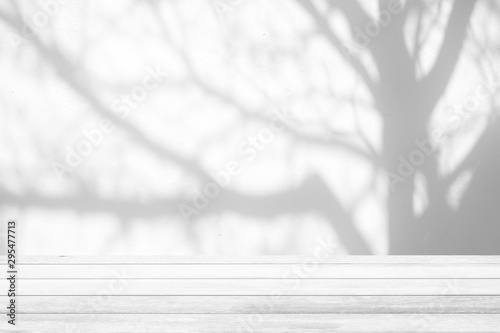Fotografia  White Wood Table with Tree Shadow on Concrete Wall Texture Background, Suitable for Product Presentation Backdrop, Display, and Mock up