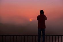 A Silhouette Of A Man On A Bri...