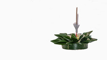 The Krathong Is Made Of Green Banana Leaves And Has Candles Embroidered On A White Background.