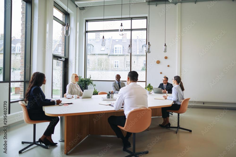 Fototapeta Diverse group of smiling businesspeople having a boardroom meeti