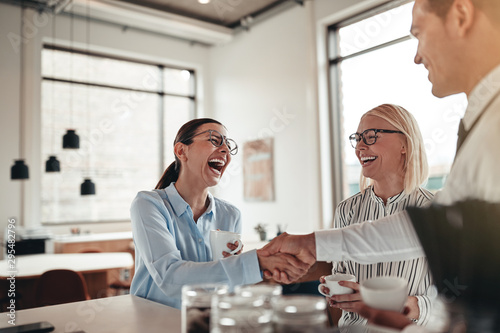 Laughing businesspeople shaking hands together during their coff