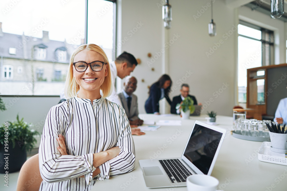 Fototapeta Smiling businesswoman working at boardroom table in an office