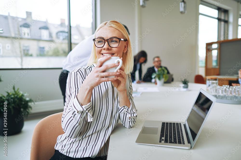 Fototapeta Smiling businesswoman enjoying a coffee while woring in an offic
